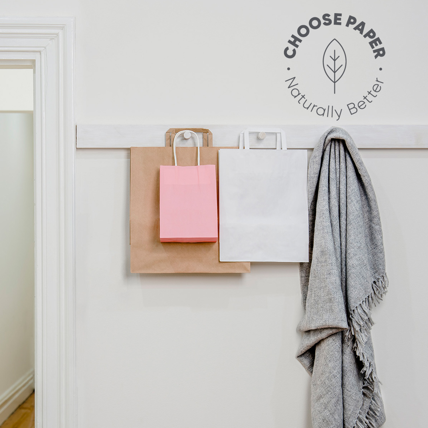Kraft, white and pink paper bags hanging on wall hooks.