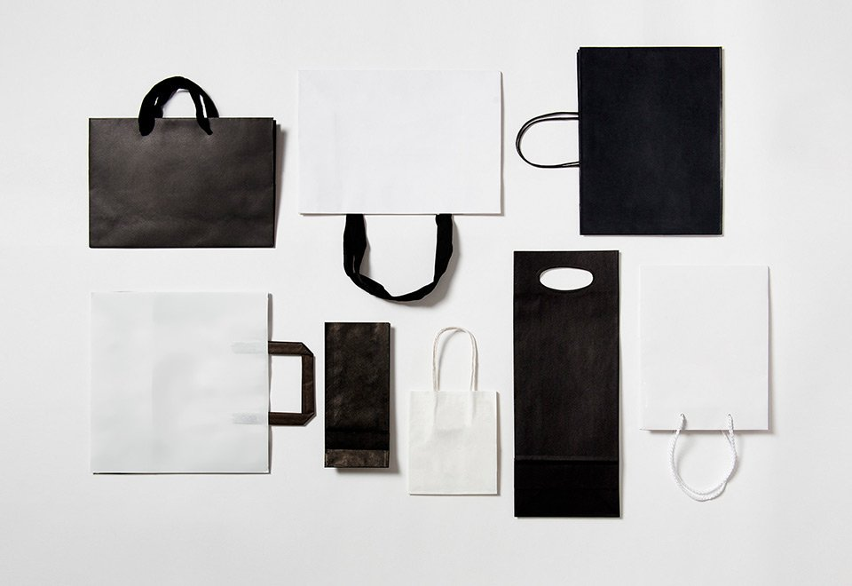 Flat lay of black and white paper bags.