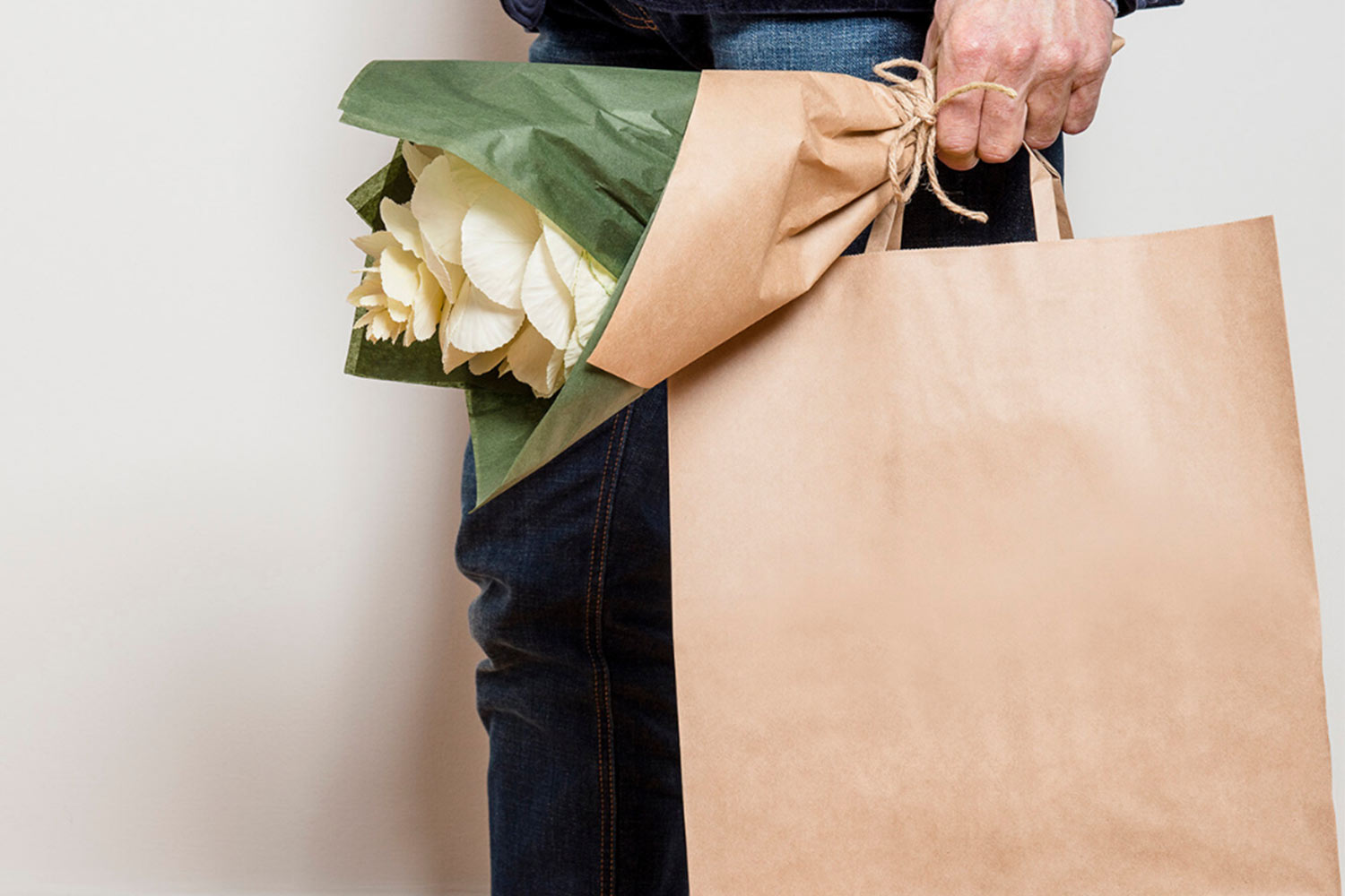 Man holding bouquet of flowers and a kraft paper gift bag.