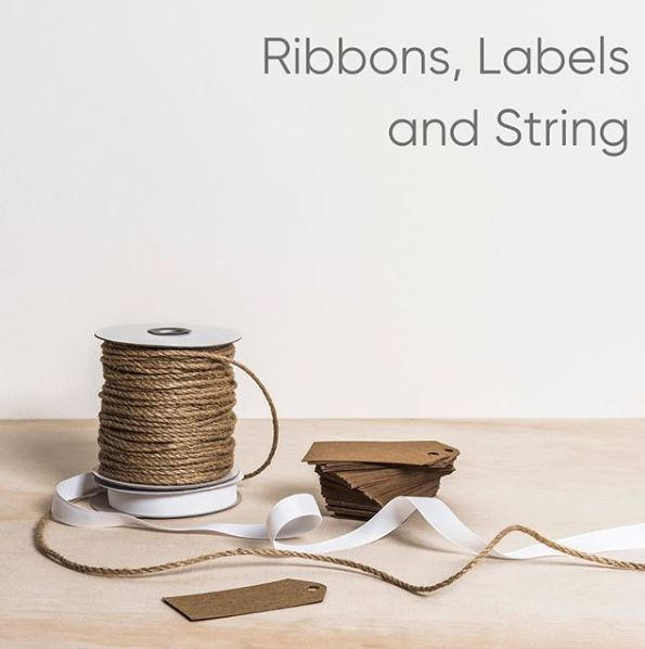 Image of jute string and white ribbon on timber desk
