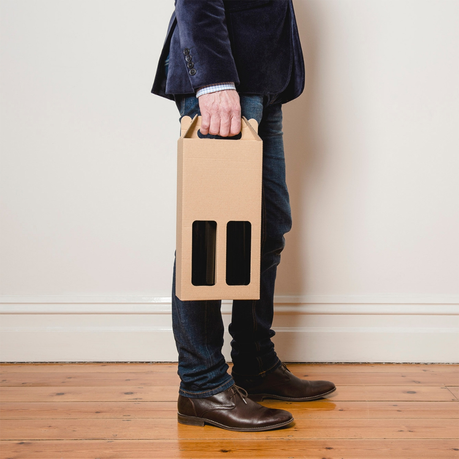 Image of a man holding wine bottles in a recyclable box