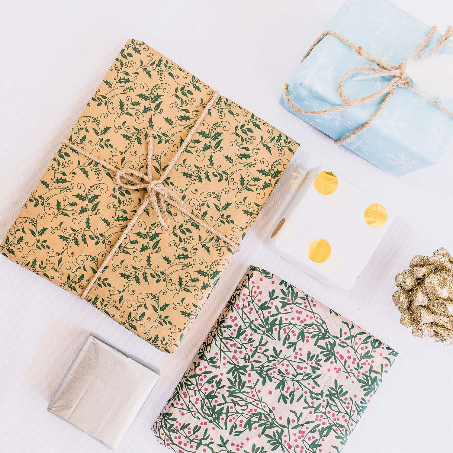 Image of four wrapped gifts in wrapping paper with different prints, two featuring jute string